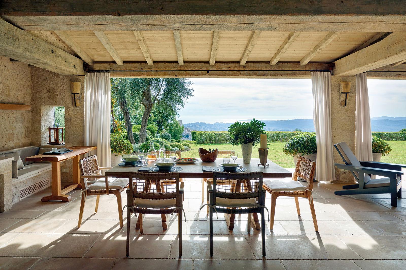 Depuis la véranda, aménagée avec des meubles et des lampes de Andrzej Zarzycki (exceptées les chaises, de la marque Unopiù), la vue sur les jardins à la française est pittoresque.
