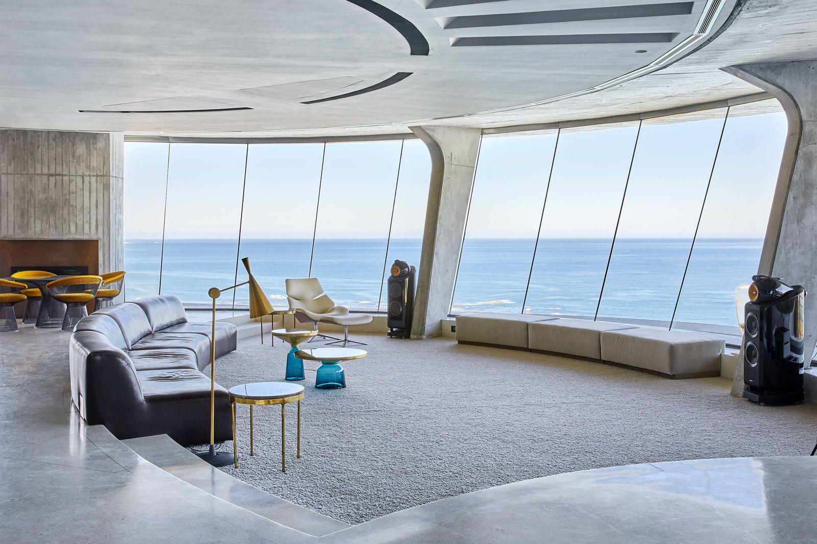 En prolongement de l'océan qu'il surplombe, le salon principal adopte les teintes sable de la plage. Au centre, le canapé incurvé en cuir brun est une création sur mesure de SRLC. Vers la lampe sur pied BEAT de Tom Dixon, la table d'appoint, en marbre et laiton, est un modèle années 1970 signé Nicos Zographos. Les tables BELL en verre soufflé sont de Sebastian Herkner pour ClassiCon et le fauteuil lounge SHRIMP avec repose-pied, de Jehs+Laub pour Cor. Devant la cheminée en cuivre, se trouvent une table et des chaises vintage de Warren Platner, Knoll.