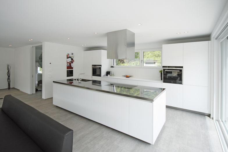 La cuisine, avec un grand espace de rangement, est séparée de la cage d'escalier par une cloison.